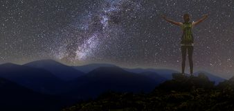 Back view of young slim backpacker tourist girl with raised arms on rocky mountain top on dark night starry sky and foggy mountain. Range panorama background royalty free stock photos