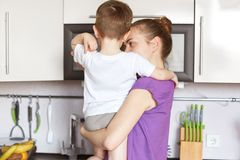 Back view of young slim mother keeps son on hands, stand at kitchen against modern furniture, going to eat supper. Busy cute woman stock photos