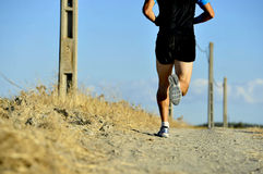 Back view of young sport man legs and feet running on countryside track with power line poles Stock Photo