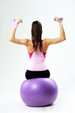 Back view of a young sport woman sitting on fitball with dumbells Royalty Free Stock Images