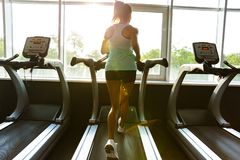 Back view of Young sports woman running on treadmill royalty free stock images