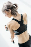 Back view of young sporty woman training with dumbbells stock photos