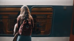 Back view of young student woman with backpack standing near in metro near the fast riding train, waiting for a trip. Stylish female traveling through the city stock video footage