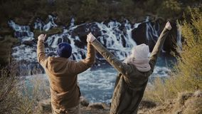 Back view of young stylish couple raising hands up and feeling happy, freedom near the waterfalls in Iceland. Back view of young stylish couple raising hands up stock video