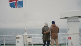 Back view of young stylish couple standing on the board of the ship with Icelandic flag. Man and woman look on the sea. Tourists traveling on the boat together stock video footage