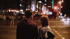 Back view of young stylish couple standing waiting the traffic light. Beautiful man and woman crossing road in evening.