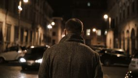 Back view of young stylish man walking late at night through the dark street, going in the evening alone. Tourist handsome male spending leisure time in lonely stock footage