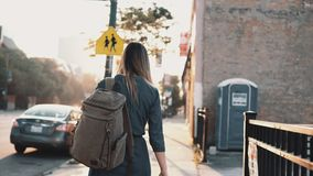 Back view of young stylish woman with backpack walking alone on sunset in summer, spending time in downtown. stock video