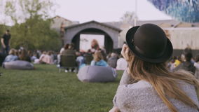 Back view of young stylish woman in hat sitting in bag-chair and looking movie in open-air cinema festival alone. Female spending leisure-time in the city stock video