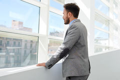Back view of young successful businessman thinking about something while looking in big office window Stock Photo