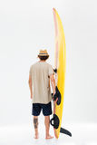 Back view a young surfer holding surfboard. Isolated on the white background Royalty Free Stock Images