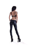 Back view of young tattooed woman in leather pants Stock Photography