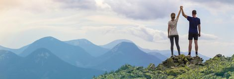 Back view of young tourist couple, athletic man and slim girl standing with raised arms holding hands on rocky mountain top. Back view of young tourist couple stock image