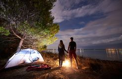 Young couple man and woman having rest at tourist tent and burning campfire on sea shore near forest royalty free stock photos