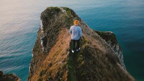 Back view young tourist man walking along dangerous path on top of Normandy coast cliff to enjoy epic seascape scenery. Successful businessman enjoying extreme stock footage