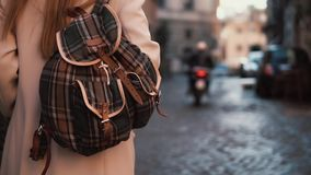 Back view of young tourist woman with backpack walking down the street. Pretty girl spending vacation in Europe. Back view of young traveling woman with stock footage