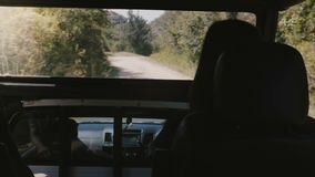 Back view young tourist woman sits in passenger saloon of safari car truck driving into the wild forest of Sri Lanka. POV shot of happy female traveler stock video footage