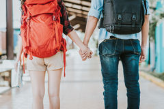 Back view of young traveler couple with backpack holding hand at train station Royalty Free Stock Photo