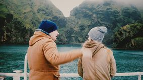 Back view of young traveling couple standing on board of the ship and talking, enjoying beautiful landscape of Iceland. stock footage