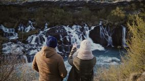 Back view of young traveling couple standing in mountains near the waterfalls in Iceland and taking photo on smartphone stock footage