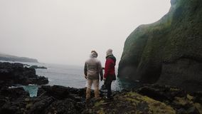 Back view of young traveling couple standing on the rocks near the sea and enjoying the beautiful view together. stock footage