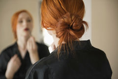 Back view of young woman applying makeup Stock Photography