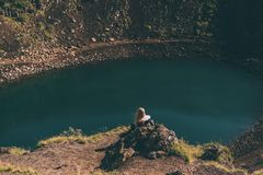 Back view of young woman. Sitting on rock and looking at beautiful crater lake in Iceland Stock Photography