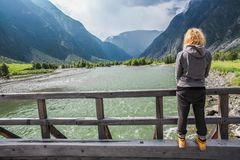 Back view of young woman. Standing on wooden bridge and looking at beautiful mountain river, Altai, Russia stock photography