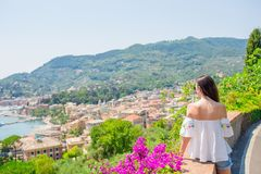 Back view of young woman background stunning town. Tourist looking at scenic view of Rapallo, Cinque Terre, Liguria royalty free stock image