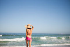 Back view of a young woman in beachwear standing in front of the Royalty Free Stock Photos