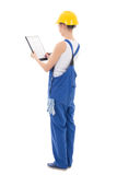 Back view of young woman builder writing something in clipboard Stock Images