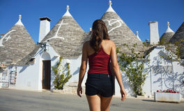 Back view of young woman choosing a trullo. Girl looking roofs of Alberobello trulli in travel in south Italy. royalty free stock photos