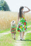 Back view of young woman covering eyes from sun and holding and little girls hand on rural dirt road Stock Image