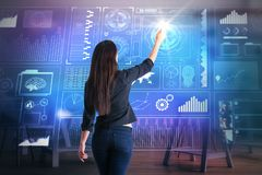 Infograph and innovation concept. Back view of young woman drawing abstract digital business hologram on blurry interior background. Infograph and innovation Royalty Free Stock Image
