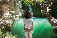 Back view of young woman enjoy waterfall on beautiful lake. Relax concept Royalty Free Stock Image