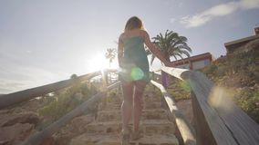 Back view. Young woman go from the beach climbing up the stairs. A woman walk up the stairs in the afternoon. stock footage