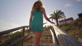 Back view. Young woman go from the beach climbing up the stairs. A woman walk up the stairs in the afternoon. stock video
