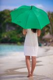 Back view of young woman with green umbrella on Stock Photography
