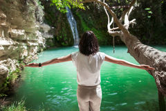 Back view of young woman with hands up enjoy waterfall on beauti Royalty Free Stock Photo