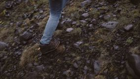 Back view of young woman hiking in rocky hills. Traveling female exploring the Iceland alone, walking through the bogs.