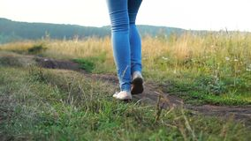 Back view of young woman in jeans legs walking by ground road on summer day. Slow motion stock footage