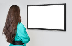 Back view of young woman looking at tv Stock Photography
