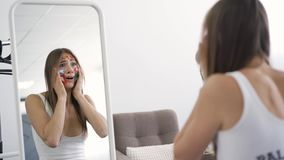Back view of young woman with multicolored social media icons on her face looking in the mirror and screaming with. Horror. Problem, emotions, depression stock video footage