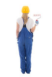 Back view of young woman painter in blue builder uniform with pa Royalty Free Stock Image