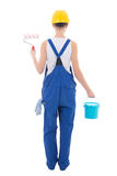 Back view of young woman painter in blue coveralls with builder' Royalty Free Stock Images