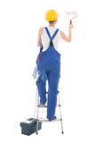 Back view of young woman painter in blue coveralls standing on l Stock Images