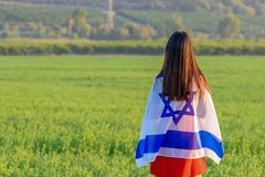 Jewish girl with flag of Israel on amazing landscape in beautiful summer. Back view Young woman patriot jewish girl standing with flag of Israel on amazing stock photography