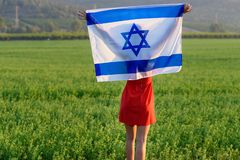 Jewish girl with flag of Israel on amazing landscape in beautiful summer. Back view Young woman patriot jewish girl standing with flag of Israel on amazing stock image