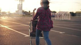 Back view of a young woman pushing the grocery cart, while her friend is sitting inside during sunset. Lens flare. Slowmotion shot stock video