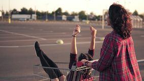 Back view of a young woman pushing a grocery cart with her girlfriend inside in the parking by the shopping mall during. Sunset. Slowmotion shot stock footage